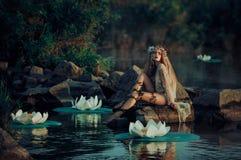 Красивая женщина в винтажном платье сидя озером стоковое изображение rf