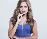 Красивая женщина в голубом платье представляя на белой предпосылке стоковое фото rf