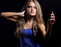 Красивая женщина в голубом платье представляя на черной предпосылке стоковое изображение