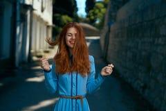 Красивая женщина в голубом платье и с красными волосами в переулке в городе Стоковые Фото