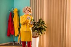 красивая женщина в заводе желтого винтажного платья моча с небольшой моча консервной банкой стоковое фото rf