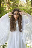 Красивая женщина в длинном белом платье стоя в лесе стоковые фотографии rf