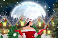 Красивая женщина в костюме santa показывать против цифров произведенной предпосылки Стоковая Фотография