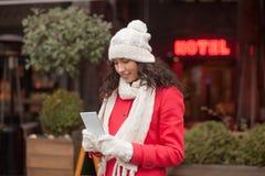 Красивая женщина в красной крышке пальто и шерстей и перчатки с smartph Стоковая Фотография