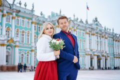 Красивая женщина в красном платье и человеке представляя положение в зиме, свадьбе в Санкт-Петербурге стоковые фотографии rf