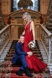 Красивая женщина в красном платье стоит с человеком, женихом и невеста, счастливыми новобрачными стоковое изображение rf