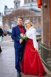 Красивая женщина в красном платье стоит с человеком, женихом и невеста, счастливыми новобрачными стоковая фотография