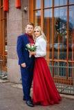 Красивая женщина в красном платье стоит с человеком, женихом и невеста, счастливыми новобрачными стоковые фотографии rf