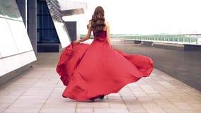 Красивая женщина в красном порхая платье видеоматериал