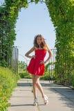Красивая женщина в красном платье в парке стоковые фотографии rf