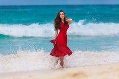 Красивая женщина в красном платье на тропическом морском побережье стоковое изображение rf