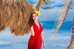 Красивая женщина в красном платье на тропическом морском побережье стоковая фотография