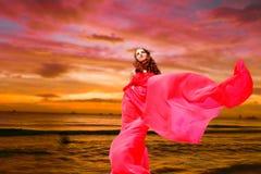 Красивая женщина в красном платье на тропическом backgr захода солнца моря Стоковые Изображения