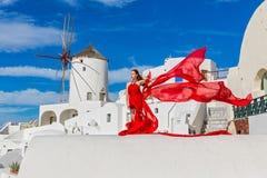 Красивая женщина в красном платье на Santorini Стоковая Фотография