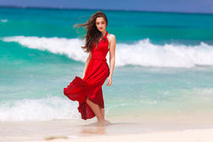 Красивая женщина в красном платье стоя на тропическом море co стоковое фото