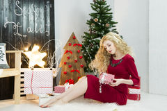 Красивая женщина в красном платье с много подарочных коробок Стоковая Фотография
