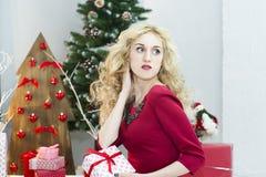 Красивая женщина в красном платье с много подарочных коробок Стоковые Фото