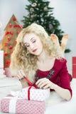 Красивая женщина в красном платье с много подарочных коробок Стоковое Изображение