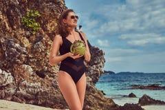 Красивая женщина в купальнике, кокос владениями при трубка, стоя на пляже около больших камней рифа, наслаждается каникулами даль Стоковая Фотография RF