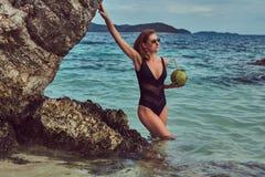 Красивая женщина в купальнике, кокос владениями при трубка, стоя на пляже около больших камней рифа, наслаждается каникулами даль Стоковое фото RF