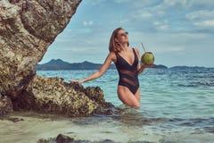 Красивая женщина в купальнике, кокос владениями при трубка, стоя на пляже около больших камней рифа, наслаждается каникулами даль Стоковые Фото