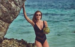Красивая женщина в купальнике, кокос владениями при трубка, стоя на пляже около больших камней рифа, наслаждается каникулами даль Стоковая Фотография