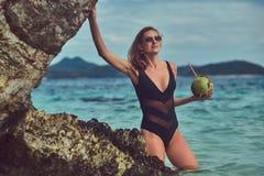 Красивая женщина в купальнике, кокос владениями при трубка, стоя на пляже около больших камней рифа, наслаждается каникулами даль Стоковое Изображение RF