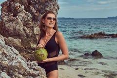 Красивая женщина в купальнике, кокос владениями при трубка, стоя на пляже около больших камней рифа, наслаждается каникулами даль Стоковые Фотографии RF