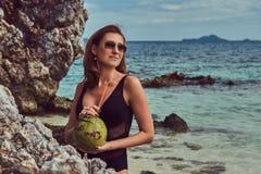 Красивая женщина в купальнике, кокос владениями при трубка, стоя на пляже около больших камней рифа, наслаждается каникулами даль Стоковые Изображения RF