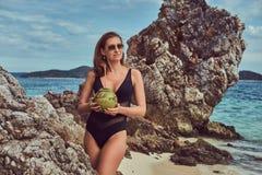 Красивая женщина в купальнике, кокос владениями при трубка, стоя на пляже около больших камней рифа, наслаждается каникулами даль Стоковое Фото