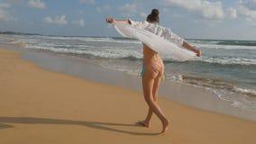 Красивая женщина в купальнике и рубашка идя на море приставают к берегу barefoot и поднятые руки Маленькая девочка идя на океан Стоковые Изображения RF