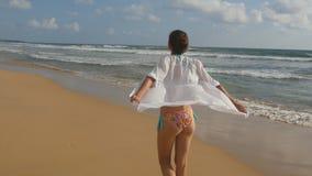 Красивая женщина в купальнике и рубашка идя на море приставают к берегу и подняли руки Маленькая девочка идя на берег океана и Стоковое Фото