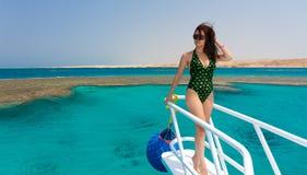 Красивая женщина в купальнике стоя на носе яхты a Стоковое Изображение RF