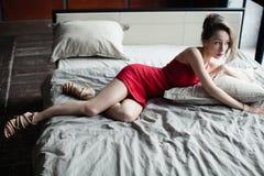 Красивая женщина в меньшем красном платье лежит на кровати Стоковое Изображение RF
