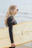 Красивая женщина в мокрой одежде держа surfboard на пляже Стоковая Фотография