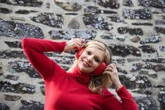 Красивая женщина в музыке красного свитера усмехаясь слушая с головой Стоковая Фотография