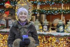 Красивая женщина в одеждах зимы с кофе в руке на предпосылке красивого bokeh напольно стоковое фото