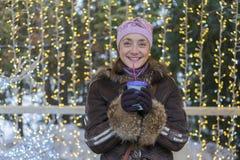 Красивая женщина в одеждах зимы с кофе в руке на предпосылке красивого bokeh напольно стоковое изображение