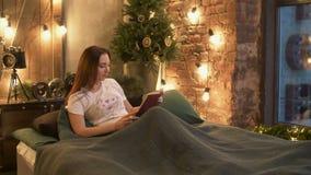 Красивая женщина в пижамах читая книгу в кровати видеоматериал