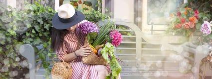 Красивая женщина в платье с приобретениями, сидит на стенде в улице города Большая корзина овощей и цветков в Стоковые Фотографии RF