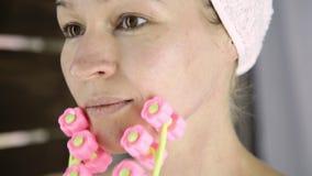 Красивая женщина в полотенце делая косметические процедуры в доме массаж стороны с massager видеоматериал