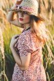 Красивая женщина в поле на заходе солнца лета Стоковые Изображения