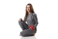 Красивая женщина в положении усаживания держа 2 красных гантели в одной руке в сером термальном нижнем белье Стоковые Изображения RF