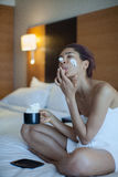 Красивая женщина в полотенце на кофе кровати выпивая с взбитой сливк Стоковые Фотографии RF