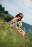 Красивая женщина в платье сидя на траве и имея потеху стоковая фотография