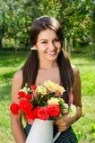 Красивая женщина в саде с цветками. Стоковое Изображение