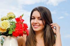Красивая женщина в саде с цветками. Стоковые Изображения