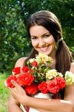 Красивая женщина в саде с цветками. Стоковая Фотография