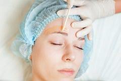 Красивая женщина в салоне курорта получая бровь epilation или коррекции стоковые изображения rf