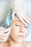 Красивая женщина в салоне курорта получая бровь epilation или коррекции стоковое фото rf
